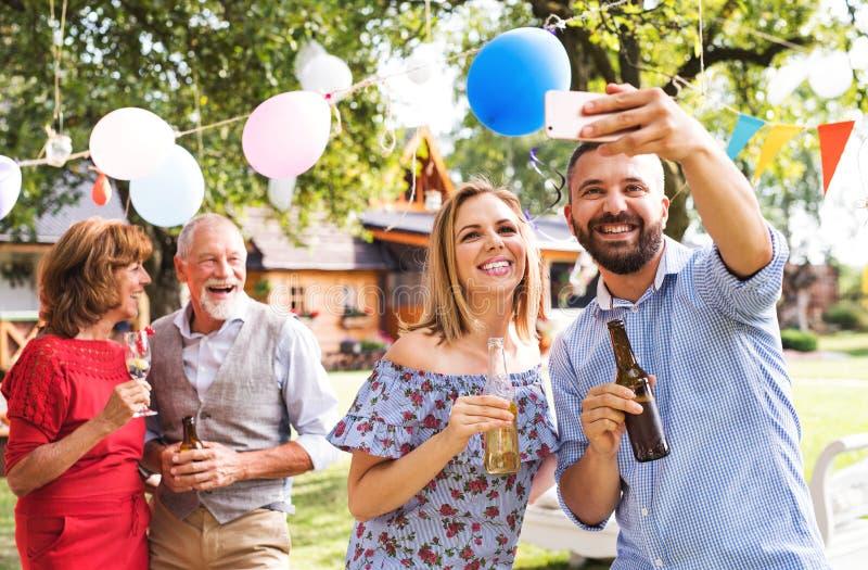 Jeunes couples prenant le selfie à une partie dehors dans l'arrière-cour, riant image stock