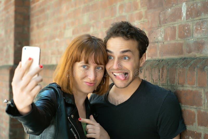 Jeunes couples prenant le selfie avec le t?l?phone portable dehors photo libre de droits