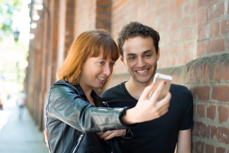 Jeunes couples prenant le selfie avec le t?l?phone portable dehors image stock
