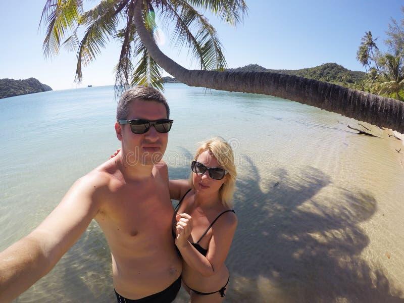 Jeunes couples prenant un bain de soleil en mer près de la paume à la plage sauvage photo stock
