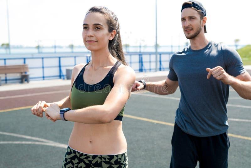 Jeunes couples réchauffant avant séance d'entraînement images stock