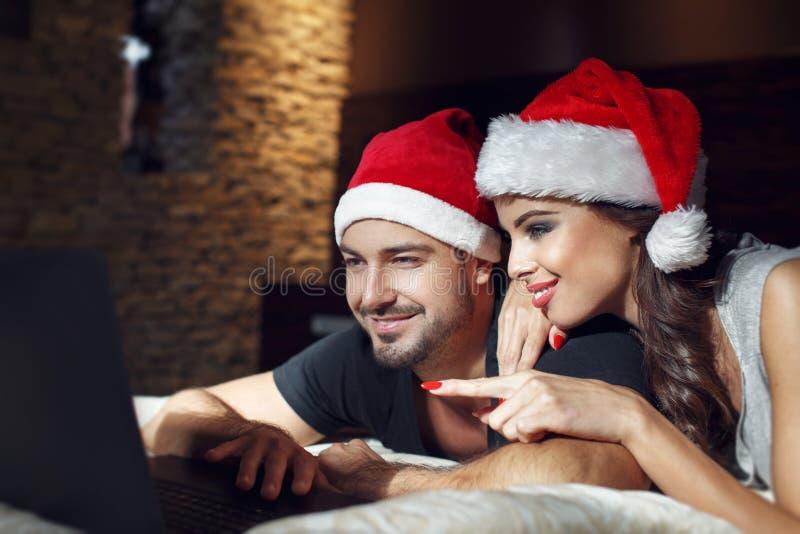 Jeunes couples recherchant le cadeau de Noël en ligne photographie stock libre de droits