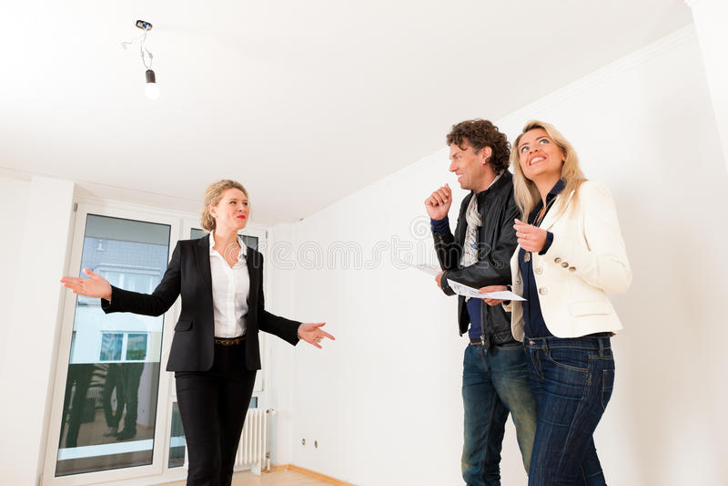Jeunes couples recherchant les immobiliers avec l'agent immobilier femelle photos stock