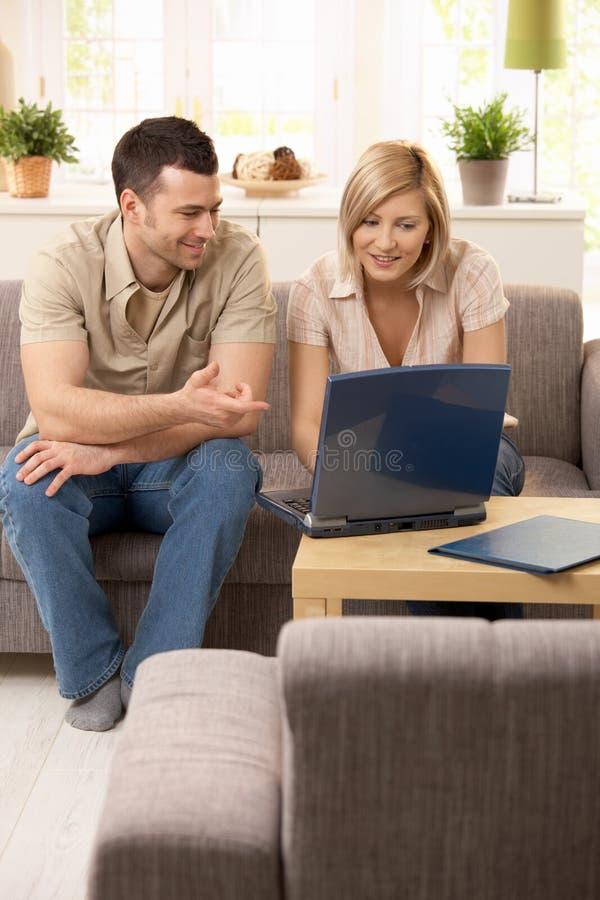Jeunes couples regardant l'ordinateur portatif images libres de droits