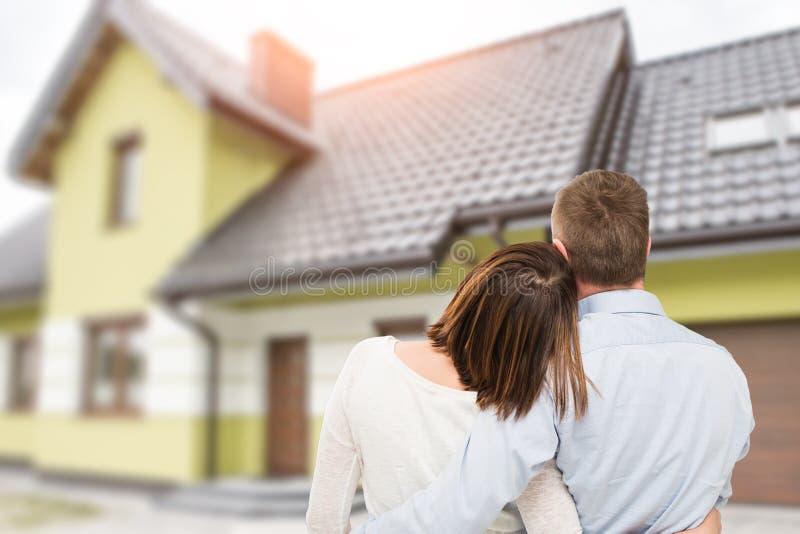 Jeunes couples regardant la maison rêveuse images stock