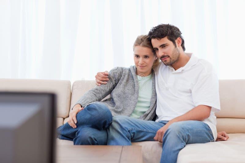 Jeunes couples regardant la TV photo libre de droits