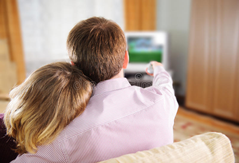 Jeunes couples regardant la TV images stock