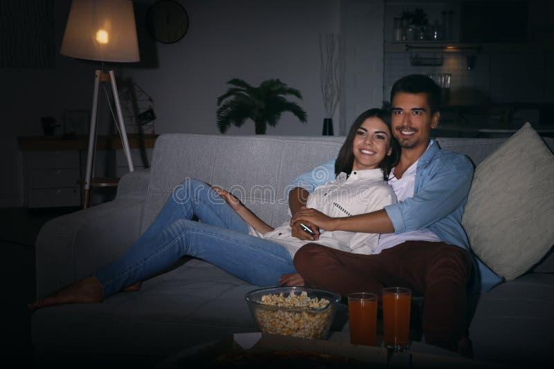 Jeunes couples regardant la TV sur le sofa la nuit image stock