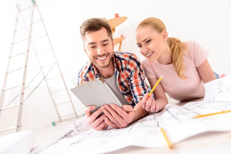 Jeunes couples regardant le comprimé images stock