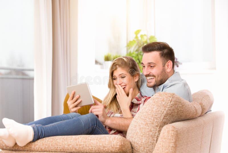 Jeunes couples regardant le comprimé et riant à la maison photo stock