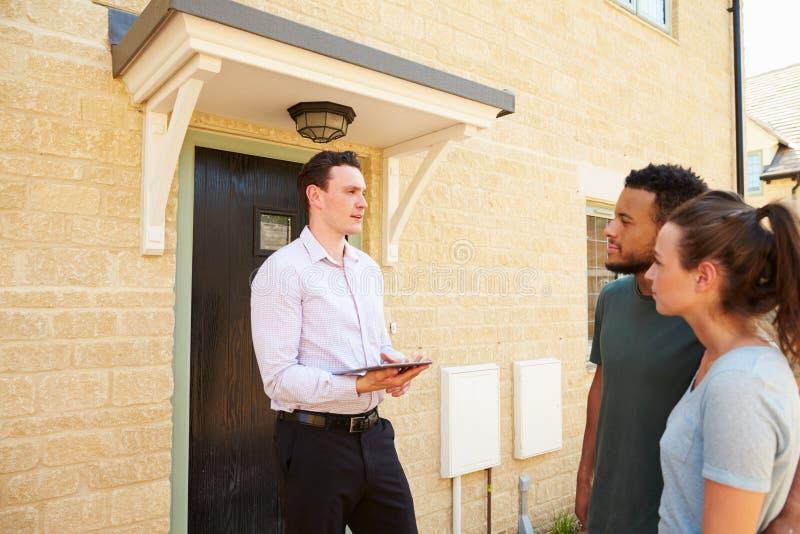 Jeunes couples regardant une maison avec le vrai agent immobilier masculin images stock