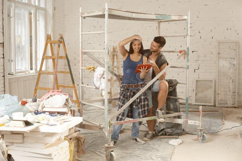 Jeunes couples remplaçant à la maison images stock