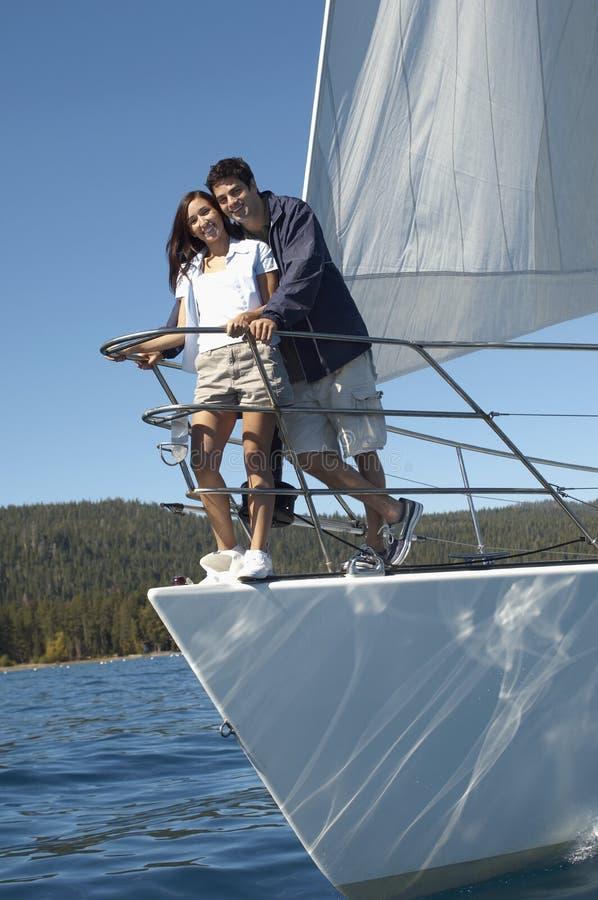 Jeunes couples restant sur le bateau à voiles images stock
