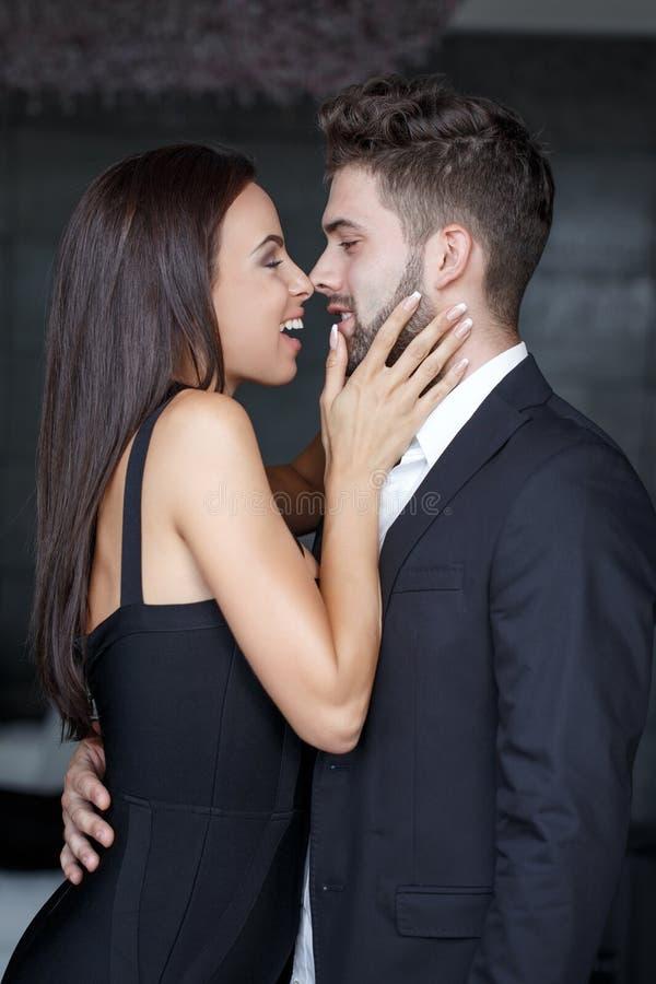Jeunes couples riant avant le baiser d'intérieur photos libres de droits