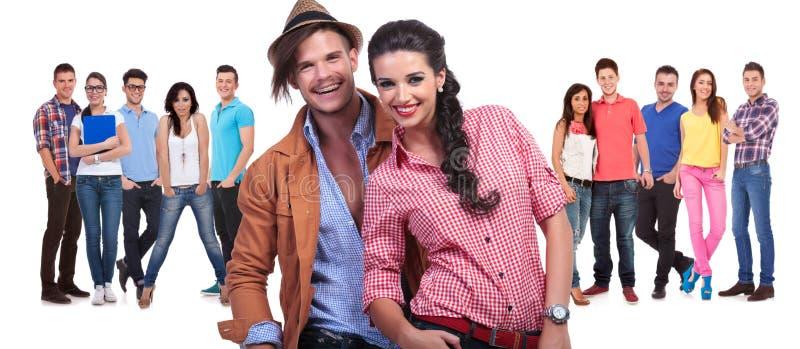 Jeunes couples riant devant un grand groupe d'amis images stock