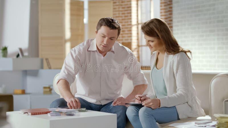 Jeunes couples riches comptant l'argent de sort, fournissant des affaires ensemble, budget de famille photos stock