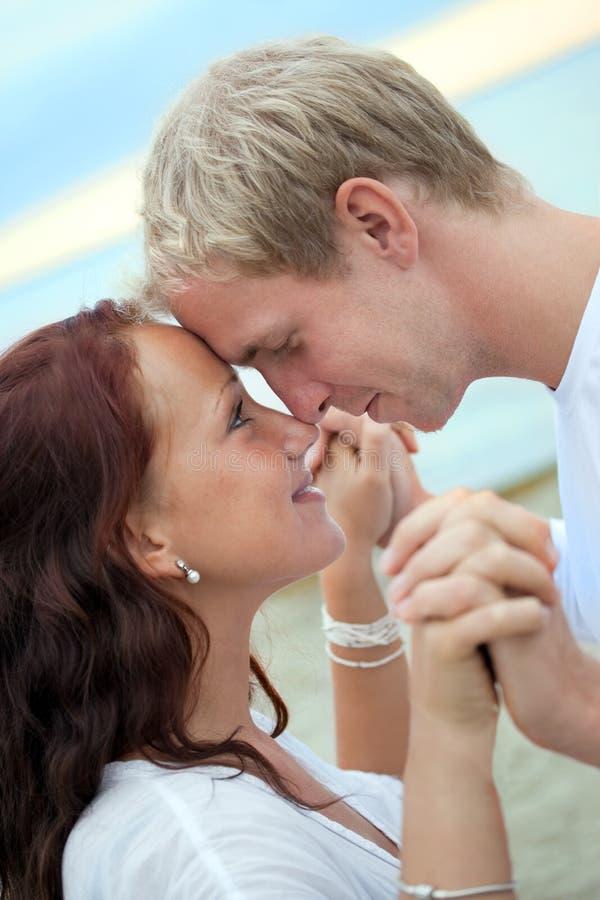 Jeunes couples romantiques ayant l'amusement sur la plage image libre de droits