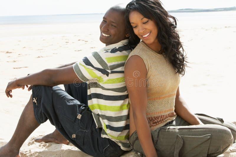 Jeunes couples romantiques détendant sur la plage ensemble photos libres de droits