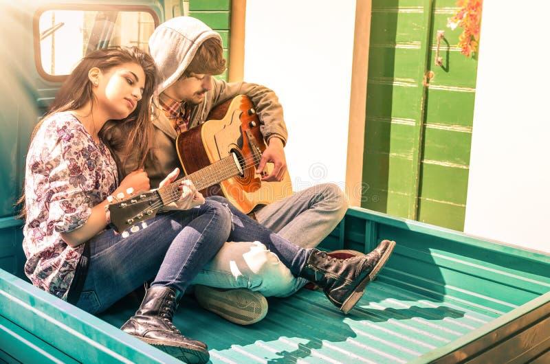 Jeunes couples romantiques des amants jouant la guitare dehors image libre de droits
