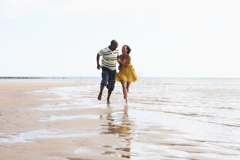 Jeunes couples romantiques fonctionnant le long du rivage photos stock