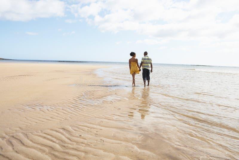 Jeunes couples romantiques marchant le long du rivage image stock
