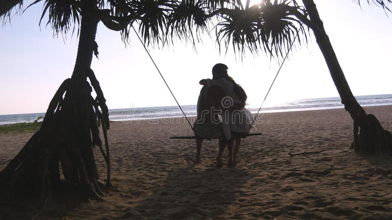 Jeunes couples romantiques se reposant ensemble sur l'oscillation à la plage et à étreindre tropicaux de mer Paires dans l'amour  image stock