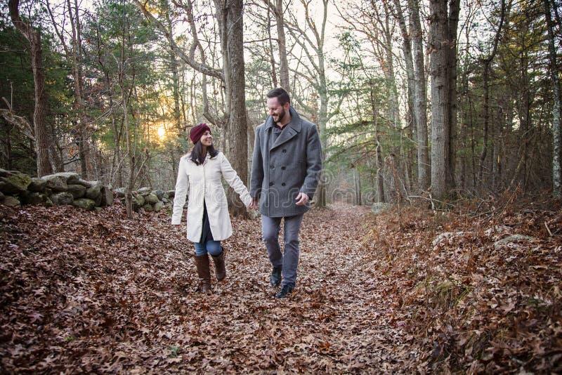 Jeunes couples romantiques tenant des mains marchant dans les bois images stock