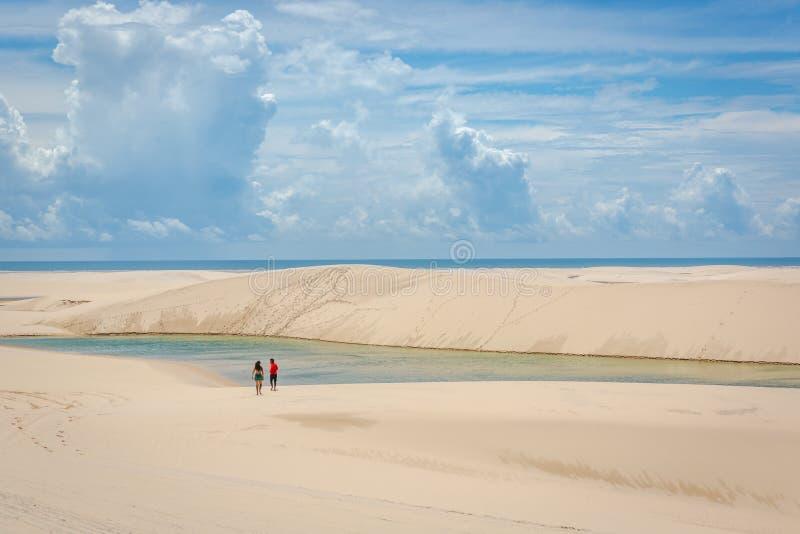 Jeunes couples se dirigeant à une piscine naturelle par les dunes arénacées au Brésil image libre de droits