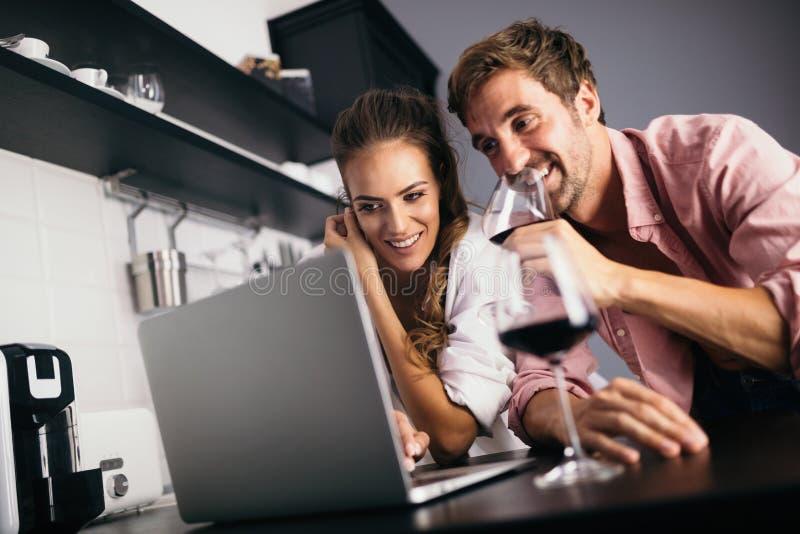 Jeunes couples se relaxant dans la cuisine avec du vin et un ordinateur portable Amour, technologie, concept humain photo stock