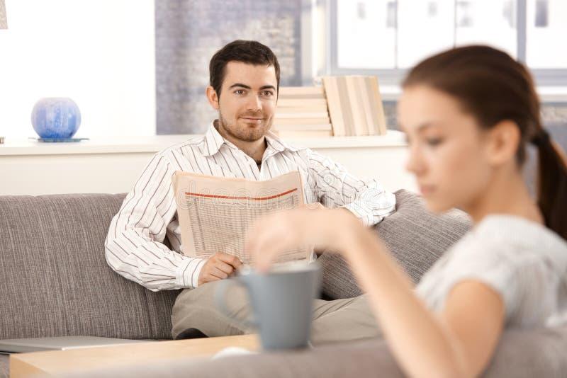 Jeunes couples se reposant dans la salle de séjour sur le sofa photo libre de droits