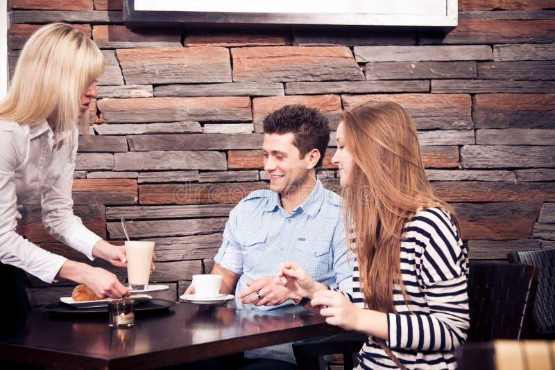 Jeunes couples se reposant dans un café photo stock