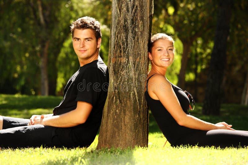 Jeunes couples se reposant en stationnement images libres de droits