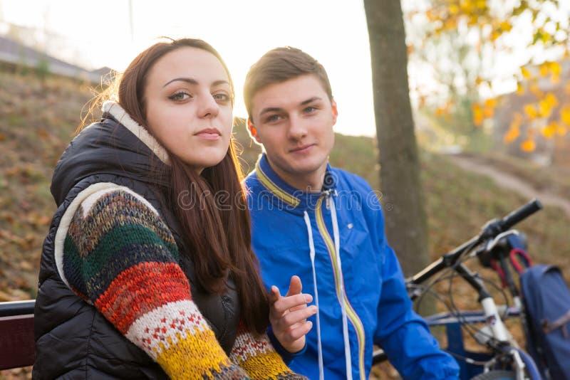 Jeunes couples se reposant ensemble sur le banc de stationnement photo libre de droits