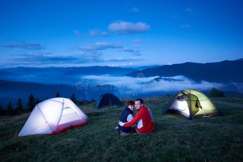 Jeunes couples se reposant près du campus de tente sur le fond du paysage de montagne images stock