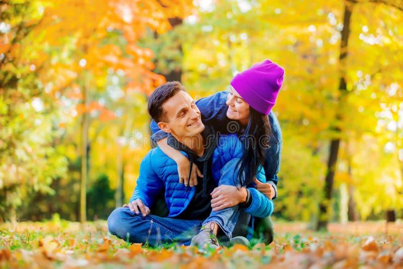 Jeunes couples se reposant sur la terre en parc de temps de saison d'automne images libres de droits