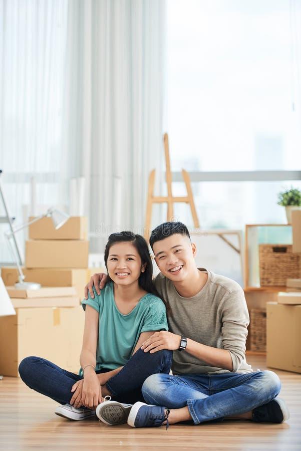 Jeunes couples se reposant sur le plancher images stock