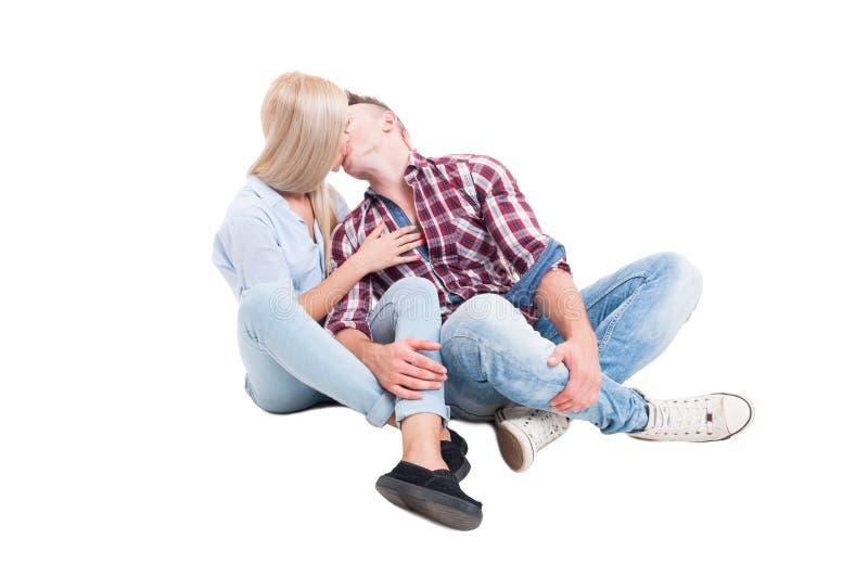 Jeunes couples se reposant sur le plancher blanc et s'embrassant images stock