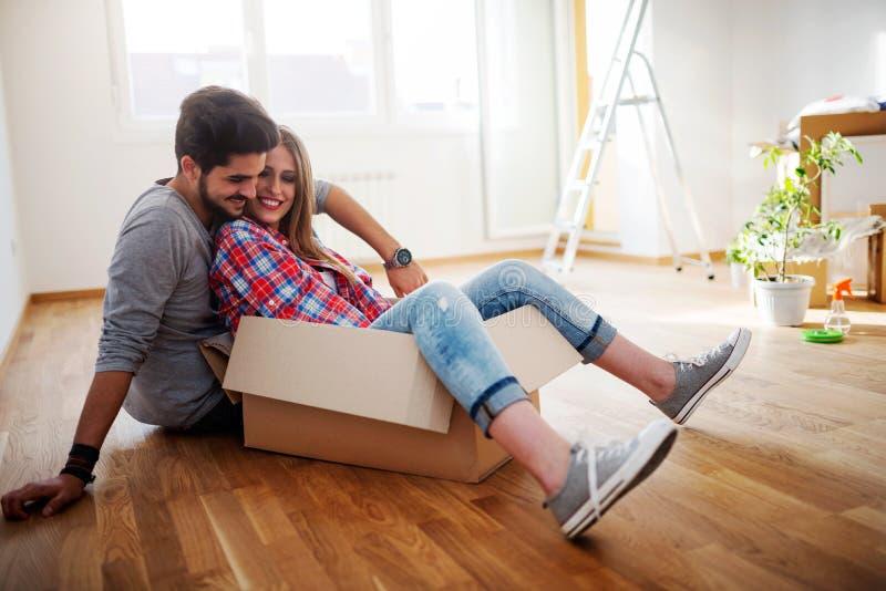 Jeunes couples se reposant sur le plancher de l'appartement vide Déplacez-vous dedans à la nouvelle maison photos stock