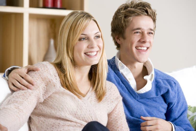 Jeunes couples se reposant sur le sofa regardant ensemble la TV images stock