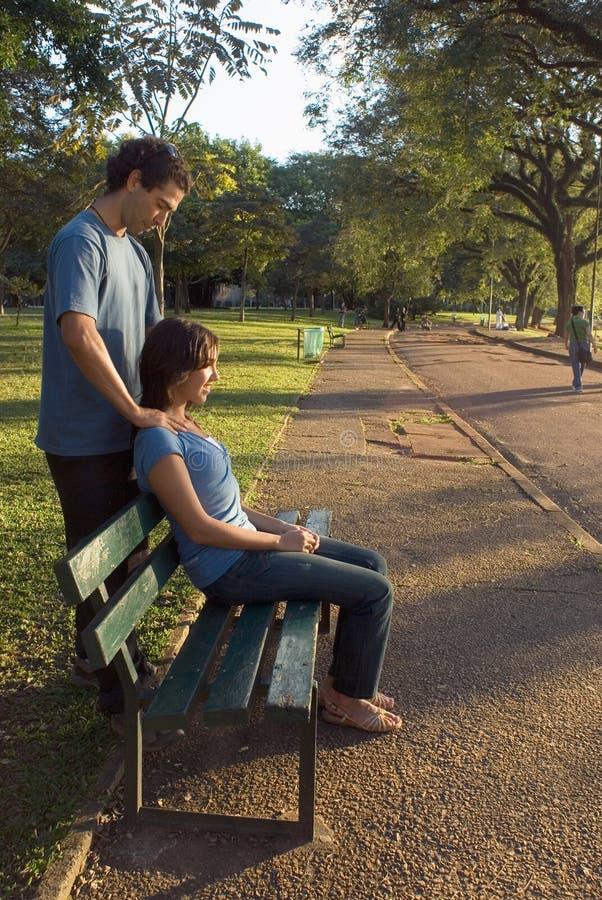 Jeunes couples se reposant sur un banc de stationnement - verticale photo stock