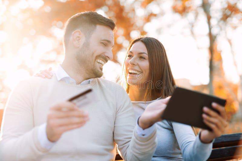 Jeunes couples se reposant sur un banc et des utilisations de parc un comprimé numérique photo libre de droits