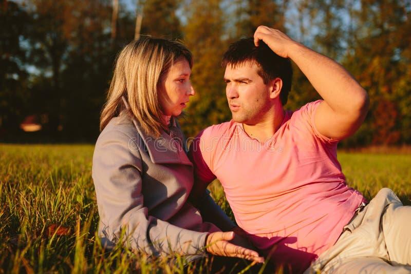 Jeunes couples se reposant sur un pré photographie stock