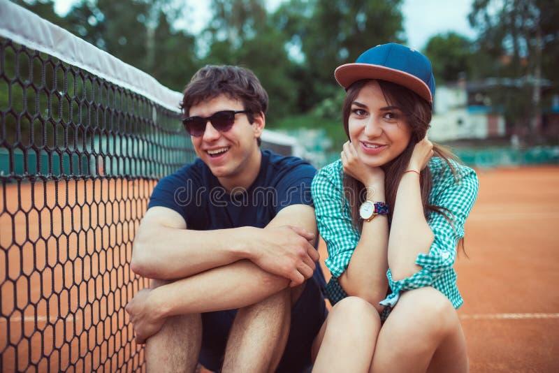 Jeunes couples se reposant sur une planche à roulettes sur le court de tennis images stock