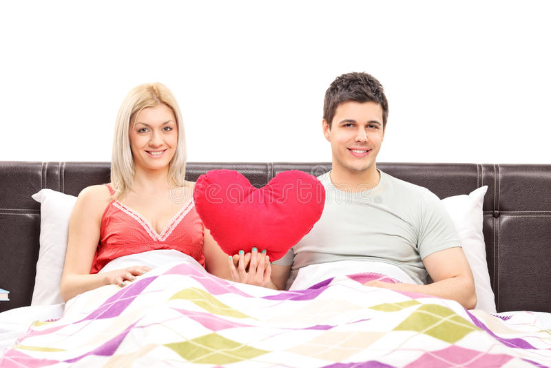 Jeunes couples se situant dans le lit et tenant un coeur rouge photo stock