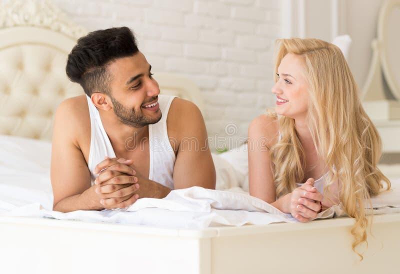 Jeunes couples se situant dans le lit regardant l'un l'autre, l'homme de sourire heureux et la femme hispaniques photo stock