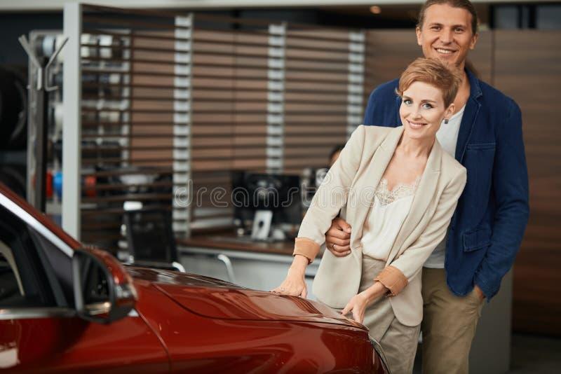 Jeunes couples se tenant au concessionnaire automobile et prenant leur décision images stock