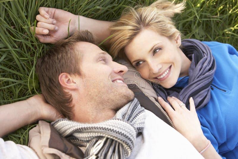 Jeunes couples se trouvant ensemble sur l'herbe photographie stock libre de droits