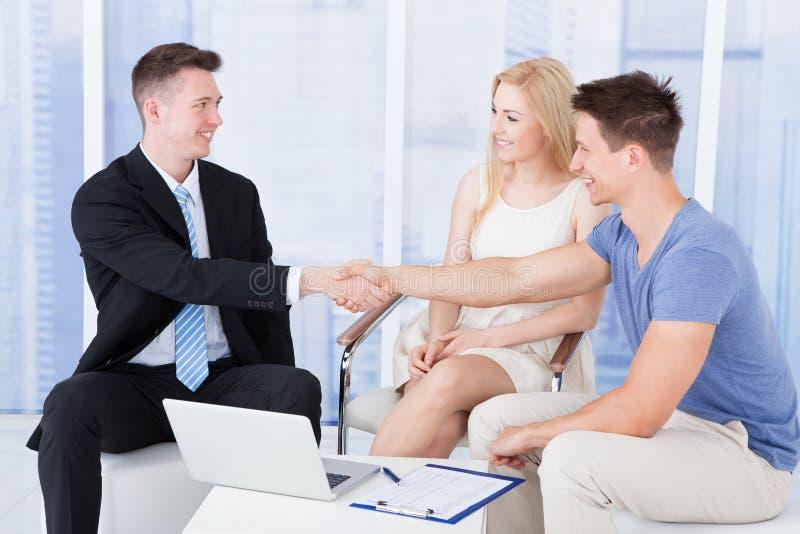 Jeunes couples serrant la main au conseiller financier photographie stock