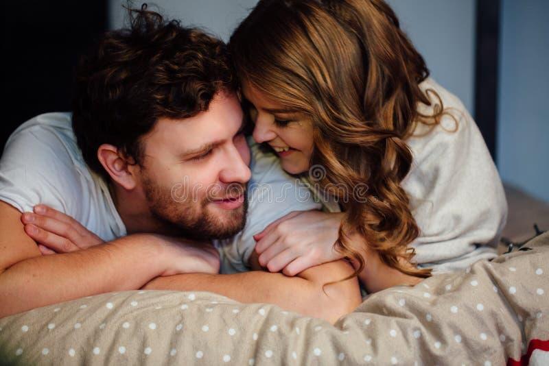 Jeunes couples sexy dans l'amour se situant dans le lit dans l'hôtel, embrassant sur les feuilles blanches, fin  photos stock