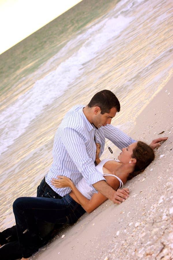 Jeunes couples sexy s'étendant ensemble sur la plage photos stock